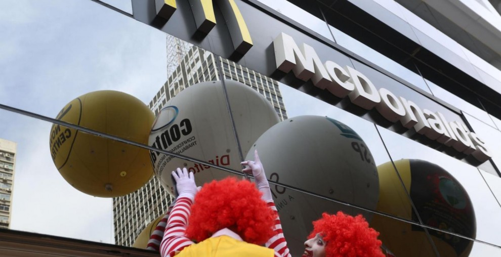 (150818) -- SAO PAULO, Aug. 18, 2015 (Xinhua) -- Two men characterized as Ronald McDonald take part in a protest outside a McDonald's restaurant at Paulista Avenue, in Sao Paulo, Brazil, on Aug. 18, 2015. Brazilian and international unions members protested on Tuesday against the largest operator of McDonald's restaurants in Latin America alleging that the firm violated the labor laws. (Xinhua/Rahel Patrasso) (jg)